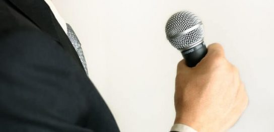 マイクでスピーチする男性