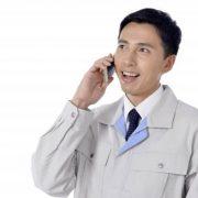 作業服を着た男性が電話中